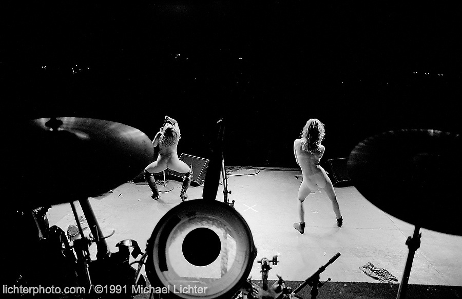 Drummer's View, Dancing at the Chip, Sturgis, SD. 1991<br /> <br /> Limited Edition Print from an edition of 50. Photo ©1991 Michael Lichter.<br /> <br /> Description: Like some sort of an ancient ritual, women got on stage to tantalize the worked up crowd. Many had never been naked in front of strangers before, but somehow, at midnight on a concert stage in the middle of the Black Hills, they choose to perform.