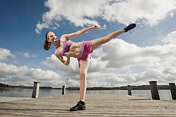 Woman exercising on jetty, Woerthsee, Bavaria, Germany