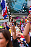 24 JANUARY 2014 - BANGKOK, THAILAND: An anti-government protestor waves a Thai flag at the Pathum Wan Shutdown Bangkok protest site while she waits for Suthep Thaugsuban. Shutdown Bangkok has been going for 12 days with no resolution in sight. Suthep, the leader of the anti-government protests and the People's Democratic Reform Committee (PDRC), the umbrella organization of the protests,  is still demanding the caretaker government of Prime Minister Yingluck Shinawatra resign, the PM says she won't resign and intends to go ahead with the election.    PHOTO BY JACK KURTZ