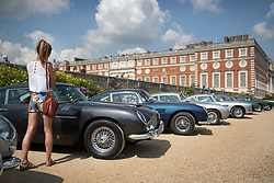 © Licensed to London News Pictures. 02/09/2017. London, UK. A visitor to the Concours of Elegance show admires a line up of Aston Martins on display in the grounds of Hampton Court Palace. The Concours of Elegance brings together, over three days, a selection of 60 of the rarest cars from around the world some of which have never been seen before in the UK. Each car owner is asked to vote on the other models on display to decide which car is considered to be the 'Best of Show'. The show also displays of hundreds of other fine motor cars, including entrants to The Club Trophy. Photo credit: Peter Macdiarmid/LNP