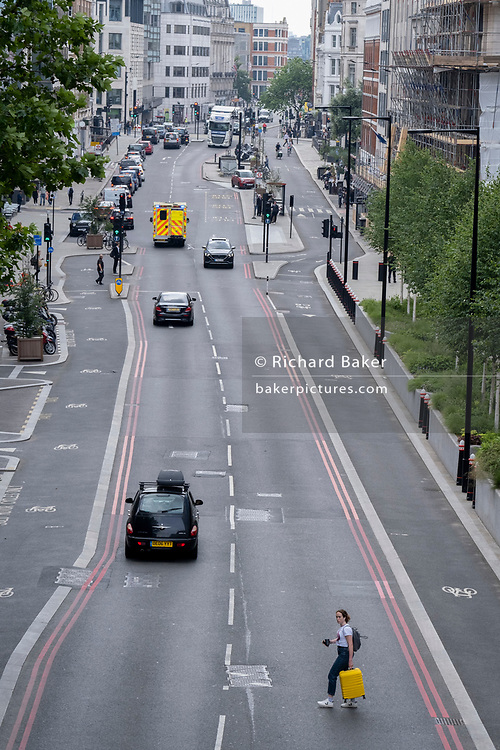 A lone woman carrying a yellow suitcase, crosses the Farringdon Road in the City of London, the capital's financial district, on 24th June 2021, in London, England. (Photo by Richard Baker / In Pictures via Getty Images) CREDIT RICHARD BAKER.