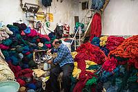 Iran, Tabriz, 23.08.2016: Ein Händler bei der Teepause in seinem Laden mit gefärbter Wolle für die Herstellung von Teppichen, Basar in Tabriz, Provinz Ost-Aserbaidschan, Nordwest-Iran.