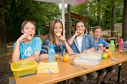 Portrait of boys and girls eating food, smiling