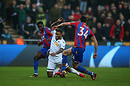 Luciano Narsingh of Swansea city © is fouled in the box by Jeffrey Schlupp (l) and Martin Kelly ® of Crystal Palace but no penalty is awarded. Premier league match, Swansea city v Crystal Palace at the Liberty Stadium in Swansea, South Wales on Saturday 23rd December 2017.<br /> pic by  Andrew Orchard, Andrew Orchard sports photography.