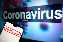 The Nintendo logo seen displayed on a mobile phone with an illustrative model of the Coronavirus displayed on a monitor in the background. Photo credit should read: James Warwick/EMPICS Entertainment