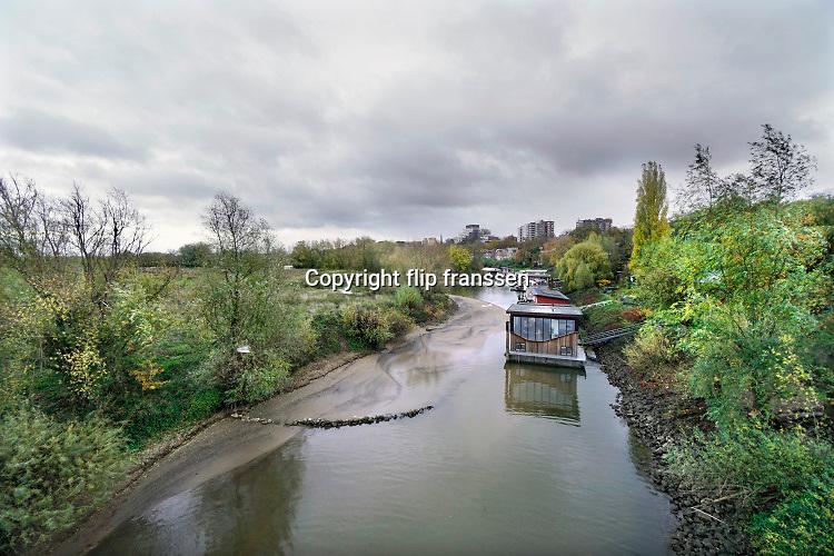 Nederland, Nijmegen, 16-11-2020 Woonboten in een rivierarm in de buurt van de stad. Links de ooijpolder. De geul moet onder de bakken van tijd tot tijd uitgebaggerd worden om de drijvende woningen niet schuin op de bodem te laten rusten  bij laagwater .Foto: ANP/ Hollandse Hoogte/ Flip Franssen