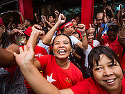 09 NOVEMBER 2015 - YANGON, MYANMAR:  People dance in the rain at NLD headquarters Monday afternoon. Thousands of National League for Democracy (NLD) supporters gathered at NLD headquarters on Shwegondaing Road in central Yangon to celebrate their apparent landslide victory in Myanmar's national elections that took place Sunday. The announcement of official results was delayed repeatedly Monday, but early reports are that the NLD did very well against the incumbent USDP.    PHOTO BY JACK KURTZ