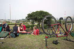 """© Licensed to London News Pictures. 30/08/2015. Calais, France.  Cyclist from """"Critical mass to Calais"""" take some rest at their arrival to Calais from London as they are to donate bicycles to the people in the refugee camp, also known as the Jungle, as well as supplies to support the life at the site. Photo credit : Isabel Infantes/LNP"""