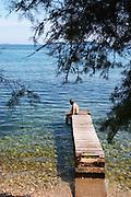 A man sitting on a wooden jetty on the stony beach looking towards the sea half hidden by pine trees. Orebic town, holiday resort on the south coast of the Peljesac peninsula. Orebic town. Peljesac peninsula. Dalmatian Coast, Croatia, Europe.