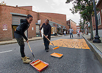 Tekla and Larry Frates paint Canal Street orange on Wednesday evening transforming it into PumpCanaly for Pumpkin Fest on Saturday.  (Karen Bobotas/for the Laconia Daily Sun)