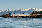 A cannery on the tiny village of Petersburg on Mitkof Island along the Wrangell Narrows in Frederick Sound with the Alaska Coast Range of mountains behind on Mitkof Island, Alaska. Petersburg settled by Norwegian immigrant Peter Buschmann is known as Little Norway due to the high percentage of people of Scandinavian origin.
