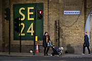 A mother walks a pet dog and pushes a child under the railway bridge at the corner of Herne Hill and Milkwood Road in SE24, and on 21st January 2021, in London, England. Herne Hill is located betwen Brixton, Dulwich Village and Camberwell and lies over the shared London boroughs of Lambeth and Southwark with a community of approximately 15,000.