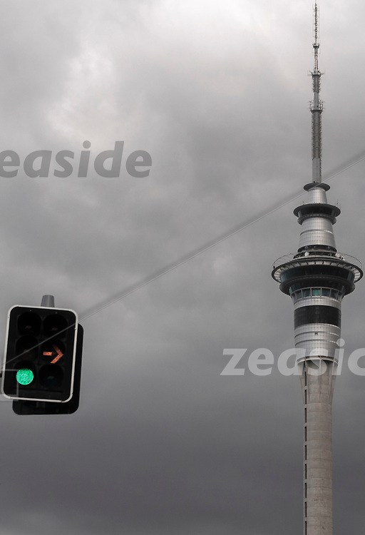 Looking up into the grey sky above Auckland, New Zealand, through the windscreen, waiting for the green light at an intersection, looking at the skytower - when not looking at the traffic lights.