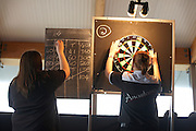 Ladies darts champion Anastasia Dobromyslova retrieves her darts after throwing arrows in a knock-out game of 501..