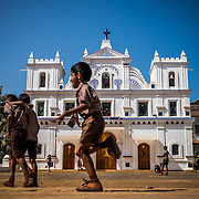 Children play in front of St. Anne's Church in Agonda vilage. The old church is a gorgeous  testament to the Portuguese history of Goa.