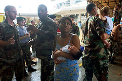 30 August, 2005. New Orleans Louisiana. Hurricane Katrina aftermath. <br /> A young mother and her baby are brought to the makeshift hospital triage unit set up at the Superdome in New Orleans. <br /> Photo Credit: Charlie Varley/varleypix.com