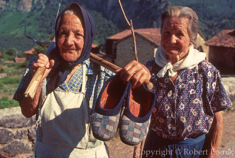 SPAIN, NORTH COAST, ASTURIAS Cantabrian Mountains and the 'Picos de Europa' near Fuente De; two elderly women helping with the harvest