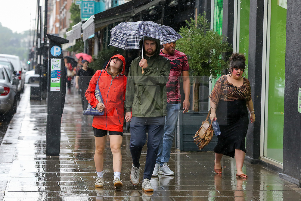 © Licensed to London News Pictures. 25/07/2021. London, UK. A couple shelter under an umbrella from a heavy downpour in north London., after the recent heatwave.  According to The Met Office, torrential thunderstorms are expected in the capital. Photo credit: Dinendra Haria/LNP