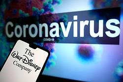 The Walt Disney Company logo seen displayed on a mobile phone with an illustrative model of the Coronavirus displayed on a monitor in the background. Photo credit should read: James Warwick/EMPICS Entertainment