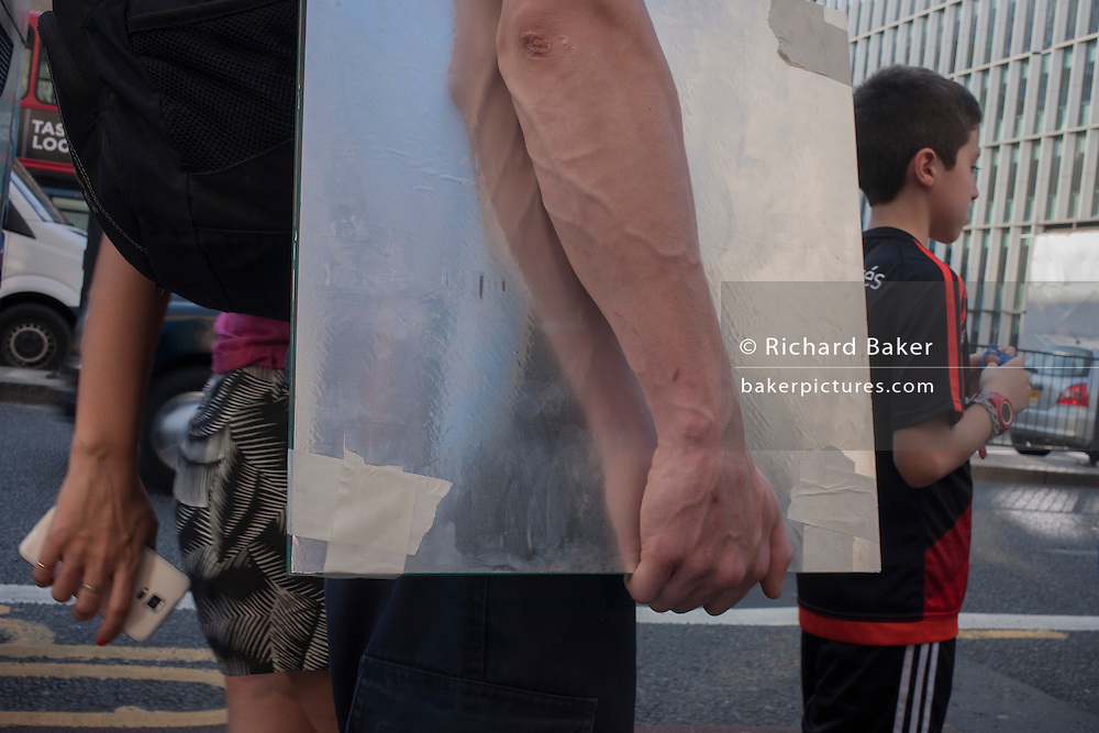 The forearm of a man carrying a reflective surface during an unusual autumn heatwave on 13th September 2016, in the City of London, England.