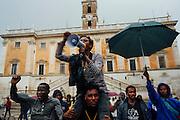 Migranti ospiti del centro d'accoglienza Baobab, protestano in piazza del Campidoglio, Roma 11 ottobre 2016. Christian Mantuano / OneShot<br /> <br /> Young migrants shout slogans under a heavy rain during a demonstration at the Campidoglio square at the Capitoline hill in central Rome on October 11, 2016. Christian Mantuano / OneShot