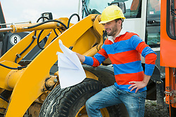 Construction worker holding construction plan in front of excavator