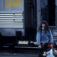 Canada, Ontario, Young woman waits with luggage at VIA Rail train station in Thunder Bay