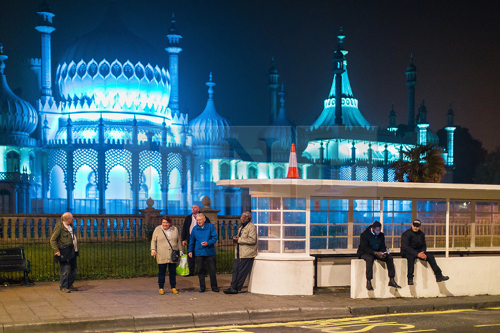 © Licensed to London News Pictures . 26/09/2017. Brighton, UK. People finishing a late shift and others catching an early bus wait at an art-deco bus stop in front of the Royal Pavilion . Revellers at the end of a night out in Brighton during Freshers week , when university students traditionally enjoy the bars and clubs during their first nights out in a new city . Photo credit: Joel Goodman/LNP