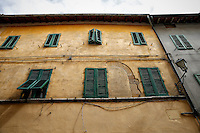 Photo of green, shuttered windows on a rustic building in San Quirico d'Orcia, Italy.