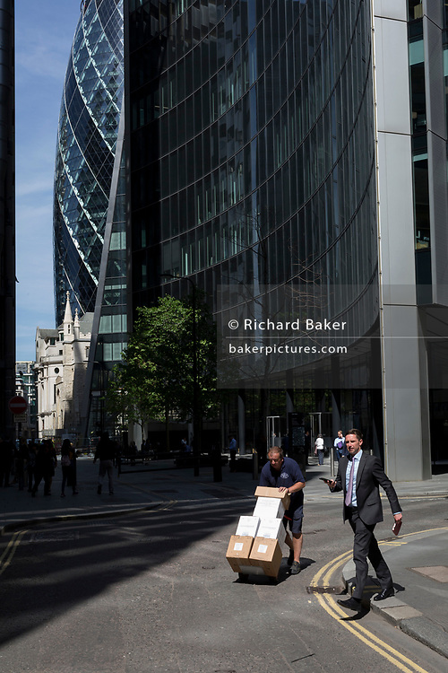 A delivery man and businessman cross paths in the City of London - the capital's financial district, on 6th June 2018, in London, England.