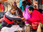 11 MARCH 2017 - KATHMANDU, NEPAL:  A Hindu priest anoints women at Swayambhu Stupa. The second most important Buddhist stupa in Kathmandu, Swayambhu Stupa is also a historic landmark and has panoramic views of Kathmandu. It is sacred to both Buddhists and Hindus. The stupa is being rebuilt because it was badly damaged in the 2015 earthquake.   PHOTO BY JACK KURTZ
