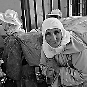 CEUTA, SPAIN - JUNE 27, 2010 : Marrocan women carrying goods queuing in the warehouses located around the pedestrian cross border of  Biutz. Thousands  of people are involved in transporting smuggled goods from Ceuta (an Spanish enclave on the North African coast) to Morocco, it is estimated that every day enter 10.000 porters, mostly women, that it make between three and five trips to Morocco with all types of products purchased on  the warehouse border area of Biutz in Ceuta, Spain .( Photo by Jordi Cami  )