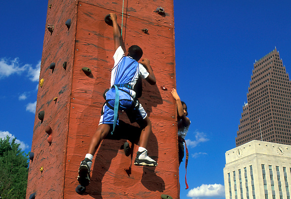 Stock photo of a boy climbing a rock wall in downtown Houston