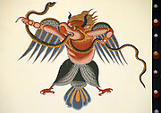 Representation of the immortal Garuda painted in traditional Bhutanese style on the wall of a house.  Garuda has the head, wings and lower body of a bird and the torso of a man. Garuda is the enemy of snakes and Nagas and they are usually seen grasped in his beak or claws. Also known as Bjachung, the devourer, Lord of Birds.  Paro,  Druk Yul, Kingdom of Bhutan. 11 November 2007.