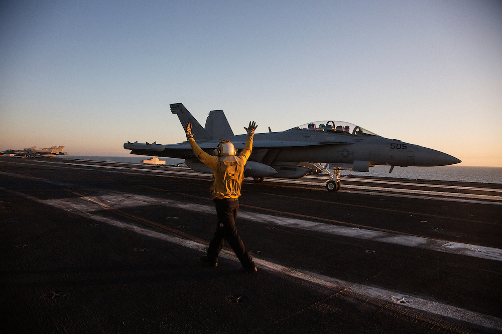 A flight deck crew member responsible for moving aircraft safely around the deck gives hand signals to an E/A-18 Growler, a jamming aircraft, moments after the plane catches a wire and lands<br /> <br /> Aboard the USS Harry S. Truman operating in the Persian Gulf. February 25, 2016.<br /> <br /> Matt Lutton / Boreal Collective for Mashable