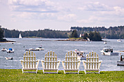 A waterfront home with adirondack chairs looking out at a beautiful view in the quaint fishing hvillage of Port Clyde, Maine.