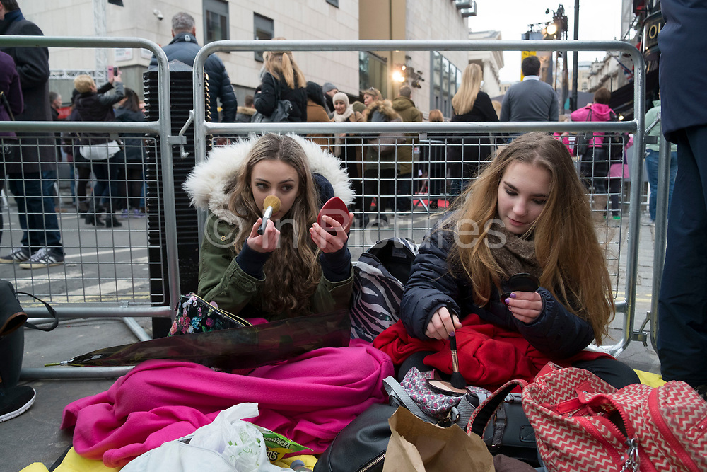Girls waiting to see their favourite movie stars outside the BAFTA Awards ceremony in London, England, United Kingdom. Izzy and Bella do their make up while they wait under blankets in the cold. Izzy has a red rose she hopes to give to Leonardo DiCaprio.