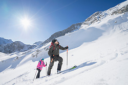 Skiers climbing up the snow mountains in bright sunlight, Bavaria, Germany, Europe