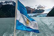 The flag of Argentina waves goodbye to Spegazzini Glacier. This flag is a triband, with three equally wide horizontal bands coloured light blue and white. The full flag with the sun is called the Official Ceremonial Flag; and the flag without the sun is considered the Ornamental Flag. On Lake Argentino in Los Glaciares National Park, we enjoyed the Glaciers Gourmet Full Day Sightseeing Cruise on board the 'Maria Turquesa' in Santa Cruz Province, Argentina, Patagonia, South America. Starting from La Soledad private port, our ship cruised to the remote and impressive Spegazzini Glacier. Lago Argentino is the biggest freshwater lake in Argentina and reaches as deep as 500 meters (1640 feet). Its outlet, the Santa Cruz River, flows into the Atlantic Ocean. Los Glaciares National Park is honored on UNESCO's World Heritage List.