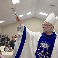 Bishop James Wall blesses the new hall and guests at the San Damiano Hall in Gallup Friday.