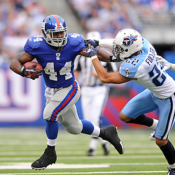New York Giants running back Ahmad Bradshaw (44) stiff-arms Tennessee Titans safety Vincent Fuller (22) during first half NFL football action between the New York Giants and Tennessee Titans at New Meadowlands Stadium in East Rutherford, New Jersey. The game is tied at half time.