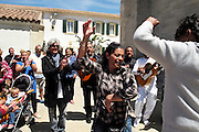 """Ricao Balliardo, with grey hair, the famous gitan guitarist and singer, dances with his family near the church <br /><br />""""Le Pelerinage des Gitans""""; the French gypsy pilgrimage of Saintes Maries de la Mer, Camargue, France<br /><br />Sainte Sara is an uncannonized saint, who legend says looked after the Christian Saints Marie Jacobe and Marie Salome, cousins of Mary Magdalene, who arrived, it is said, on the shores of the Camargue in a rudderless boat. Saint Sara is the patron saint of gypsies who come from far and wide to see her. There are even paintings of Sara as 'Kali' the black saint in Eastern Europe. Sara may have been the priestess of 'Ra' the sun-god or even servant girl to the Christian saints. No-one really knows.<br /><br />For a few weeks of the year, Roma, Gitan and Manouche gypsies come from all over Europe in May, camping in caravans around Saintes Maries de la Mer. It is a festive time where they play music, dance, party and christen their children. They all go to see Saint Sara in the crypt, kissing or touching her forehead. Many put robes on her shoulders, making her fat for the procession. In the main Gypsy procession of the 24th May, Saint Sara is allowed to leave her crypt, beneath the church, and is carried from the church to the shores of the mediterranean and back again. One day a year she is free from her prison. Hundred's of years ago the Gypsies used not even to be allowed into the church, only into the crypt like Sara...<br /><br />Roma gypsies still suffer oppressive prejudice and racism and are one of the ethnic groups the most persecuted and marginalised across Europe. The festival is one of the times where they celebrate with people of all races, their faith and traditions"""