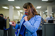 "13 OCTOBER 2020 - DES MOINES, IOWA: THERESA GREENFIELD, the Democratic candidate for the US Senate from Iowa, puts an ""I voted"" sticker on her jacket after dropping off her ballot in the Polk County Auditor's office. Greenfield, the Democratic candidate for US Senate, dropped off her completed ballot at the Polk County Auditor's Office in Des Moines. Greenfield is running against incumbent US Senator Joni Ernst, a Republican. Greenfields holds a slight lead over Ernst in recent polling.         PHOTO BY JACK KURTZ"