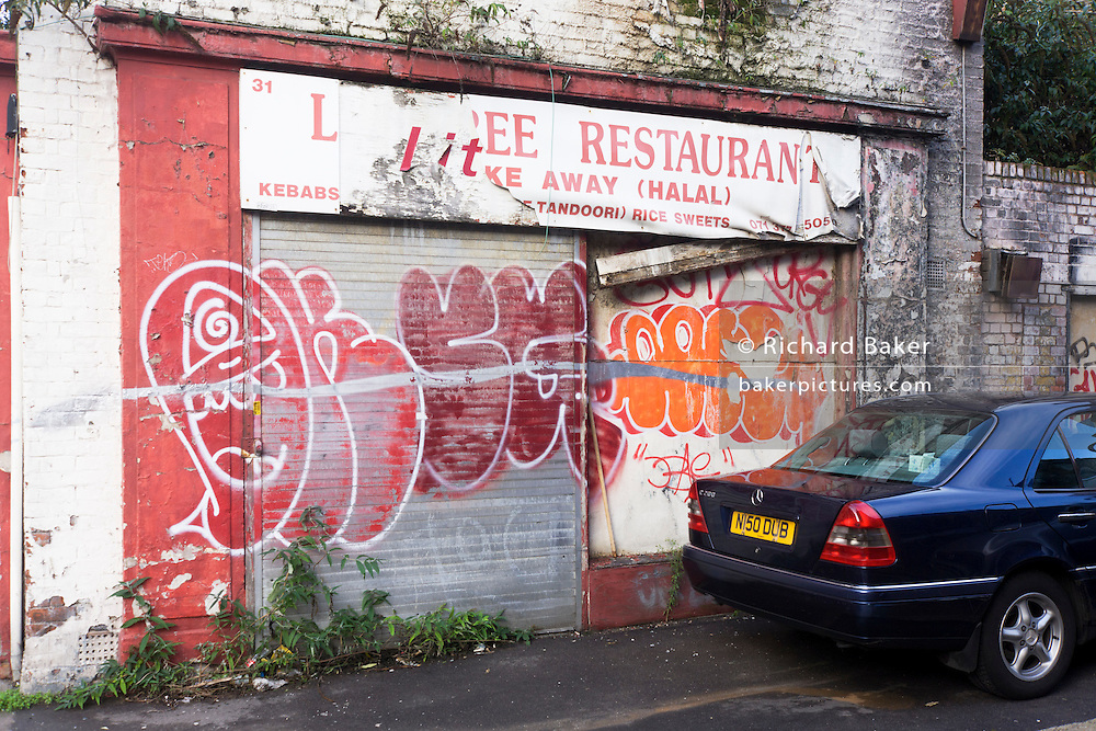 Mercedes car parked by derelict restaurant business left to decay on Toynbee Street, Tower Hamlets, East London.