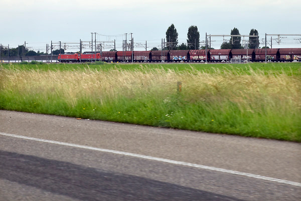 Nederland, Andelst, 12-6-2018 Een goederentrein rijdt langs de snelweg a15 over de betuweroute. De locomotief rijdt op stroom, elektriciteit . Foto: Flip Franssen