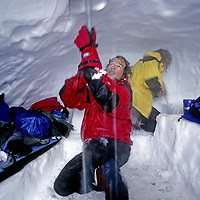 CORDILLERA SARMIENTO EXPED., Tyler Van Arsdell digs out storm-choked snow cave (Patagonia,Chile). Peter Garber bkg.(MR)