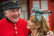 A Chelsea Pensioner with a supporter of the RAF Benevolent Fund, with a hat commemorating the 80th anniversary of the Spitfire - The opening day of th Chelsea Flower Show.