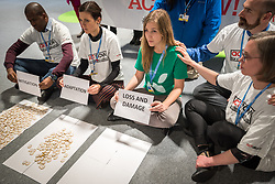 """11 December 2019, Madrid, Spain: ACT Alliance, Lutheran World Federation and World Council of Churches participants at COP25 illustrate the lack of balance in finance of the global climate response, where most ofthe finance is put into mitigation, some into adaptation, but very little into loss and damage, even though 'that's where the people are'. 'What do we want? Climate justice. When do we want it? Now!"""" they chanted, as Erika Rodning from the Evangelical Lutheran Church in Canada held a sign reading 'Loss and Damage' in front of a table empty of finance."""