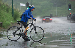 © Licensed to London News Pictures. 06/07/2012..Saltburn, Cleveland, England...After a night of heavy rain a cyclist encounters deep puddles along the sea front road in Saltburn, Cleveland. ..Photo credit : Ian Forsyth/LNP