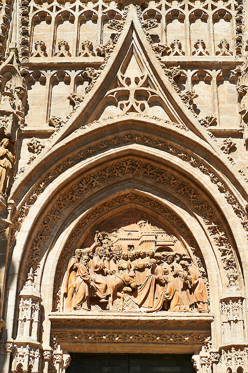 Christ's Entry into Jerusalem by Lope Marin in 1548 on the Gothic Puerta de Campanilla entrance door of the Cathedral of Seville, Spain . The Royal Alcázars of Seville (al-Qasr al-Muriq ) or Alcázar of Seville, is a royal palace in Seville, Spain. It was built by Castilian Christians on the site of an Abbadid Muslim alcazar, or residential fortress.The fortress was destroyed after the Christian conquest of Seville The palace is a preeminent example of Mudéjar architecture in the Iberian Peninsula but features Gothic, Renaissance and Romanesque design elements from previous stages of construction. The upper storeys of the Alcázar are still occupied by the royal family when they are in Seville. <br /> <br /> Visit our SPAIN HISTORIC PLACES PHOTO COLLECTIONS for more photos to download or buy as wall art prints https://funkystock.photoshelter.com/gallery-collection/Pictures-Images-of-Spain-Spanish-Historical-Archaeology-Sites-Museum-Antiquities/C0000EUVhLC3Nbgw <br /> .<br /> Visit our MEDIEVAL PHOTO COLLECTIONS for more   photos  to download or buy as prints https://funkystock.photoshelter.com/gallery-collection/Medieval-Middle-Ages-Historic-Places-Arcaeological-Sites-Pictures-Images-of/C0000B5ZA54_WD0s